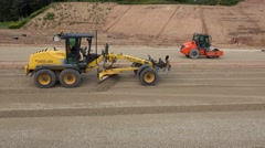 Grader machine and roller leveling rubble stones on new road construction site Stock Footage