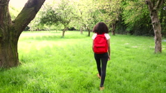 Mixed race African American girl teenager female hiking with red backpack Stock Footage