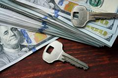 Keys and money on a table. Mortgage loan concept. Stock Photos