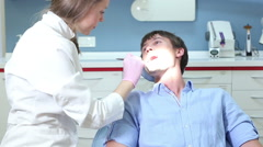 Female dentist doing routine check up to smiling male patient Stock Footage