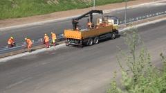 Skilled workers men mount safety steel barrier between highway lane Stock Footage