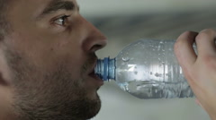 Face of the tired young man drinking water. Close up Stock Footage
