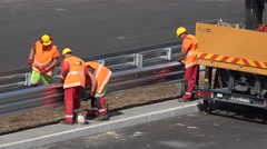 Skilled workers men brigade install safety barrier between freeway road lane Stock Footage