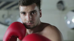 Young boxer wipes sweat from his forehead and looks into the camera lens. Stock Footage