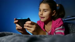 Teen girl playing kid portable video online game a console kid at night indoors Stock Footage