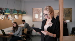 4k. young beautiful blonde businesswoman uses a touchscreen tablet in the modern Stock Footage