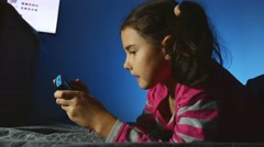 Teen girl playing portable kid video online game a console kid at night indoors Stock Footage