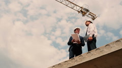 Men looks at building plan at construction site Stock Footage