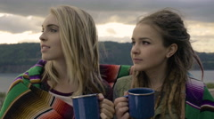 Women Share Blanket, Chat And Drink From Camping Mugs, Beautiful River Behind Stock Footage
