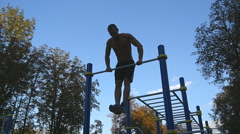 Young athlete doing chin-ups on horizontal bars outdoor. Slow motion Stock Footage