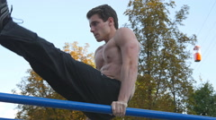 Athletic man exercise the abdominals on bar in city park.  Slow motion Stock Footage
