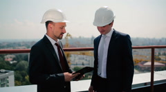 Two men in helmet talk at the roof Stock Footage
