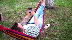 Man swinging in a hammock, make selfie, young man photographing themselves by Stock Footage