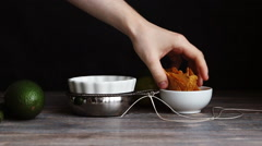 Putting nachos - mexican corn chips - in to a porcelain bowl. Stock Footage