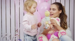Mother plays with her daughter with toys and baloons in slow motion Stock Footage