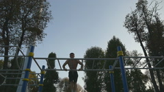 Strong muscular man doing muscle ups in a park.  Slow motion Stock Footage