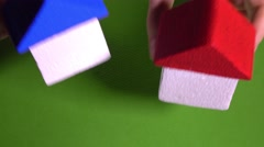 Real estate agent placing toy houses with red and blur roofs against green Stock Footage