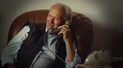 Old retired man talking at the phone and smiling: relaxed old man at home  Stock Footage