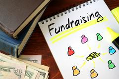 Fundraising written in a notepad. Charity concept. Stock Photos