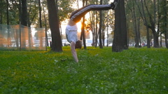 Strong muscular man doing a handstand in park at sunset. Workout sport lifestyle Stock Footage
