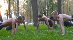 Group of athletic men doing push ups on green grass in city park. Slow motion Stock Footage