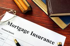 Mortgage insurance policy with a book and a pen. Stock Photos