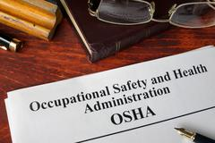 Occupational Safety and Health Administration  OSHA  and a book. Stock Photos