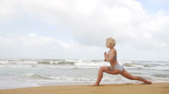 Girl practicing yoga and breathing near the indian ocean Stock Footage