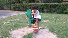 Little girl having fun on the swing in the park for children Stock Footage