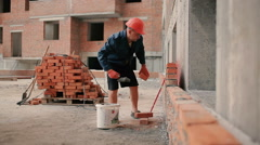 The man build the brick wall at the building site Stock Footage