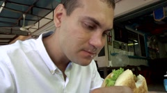 Caucasian man eat burger with hunger, slow motion Stock Footage