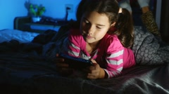 Teen girl playing portable video game a console kid at night indoors Stock Footage