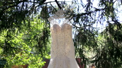 Beautiful wedding dress hanging on a green tree. The sun's glare. Stock Footage