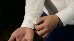 Elegant man buttoning the cuffs of his shirt. Stock Footage