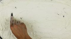 Young man writes a word recipe on white flour Stock Footage