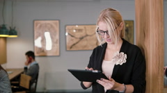 Young beautiful blonde businesswoman uses a touchscreen tablet in the modern Stock Footage