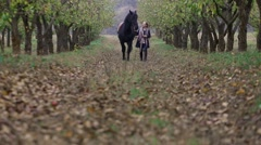 Girl in autumn garden with a black horse Stock Footage