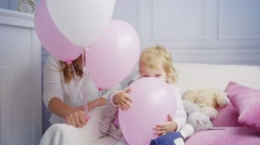 Daughter plays with air baloons having fun near mom Stock Footage