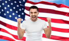 Angry man showing fists over american flag Stock Photos
