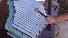 A woman striking random notes on a xylophone Stock Footage
