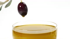 A drop of olive oil falling from one black olive Stock Footage