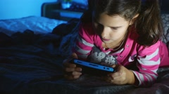 Teen girl kid playing a portable video game console at night indoors Stock Footage