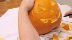 Man Carves a Mouth in a Jack 'o' Lantern Stock Footage