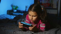 Teen playing girl portable video game a console kid at night indoors Stock Footage