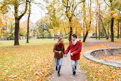 Happy young couple running in autumn park Stock Photos