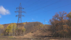 High-voltage transmission line crossing nature reserve filmed with blue sky a Stock Footage