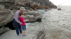 Senior man teaching to child how fishing with rod Stock Footage