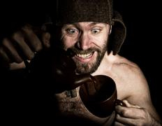 Dark portrait of scary evil sinister bearded man with smirk, he pours brandy in Stock Photos