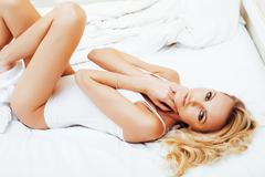 Young pretty blond woman in bed covered white sheets smiling che Stock Photos