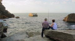 Senior couple fishing with rod on the sea Stock Footage